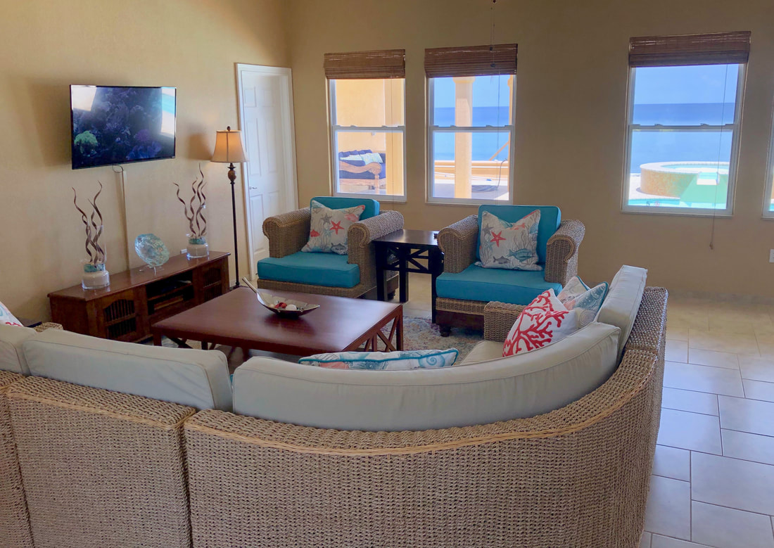 Large seagrass sectional with tropical decor in open living room with view to pool deck and sea beyond.